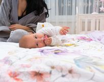 Cute baby frolicking on bed with mother in morning. A cute baby frolicking on bed spread with mother in the morning royalty free stock photography