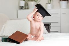 Cute baby genius baby in university graduation cap rubbing forehead and looking in camera. Concept of early child. Baby genius baby in university graduation cap royalty free stock photography