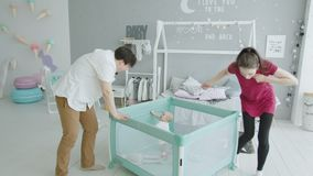 Cute baby getting up in playpen looking at parents stock footage