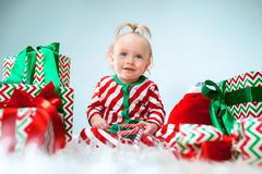 Free Cute Baby Girl 1 Year Old Near Santa Hat Posing Over Christmas Background. Sitting On Floor With Christmas Ball. Holiday Royalty Free Stock Image - 134193566