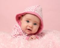 Cute baby girl. Portrait of adorable baby girl on pink blanket and background, lying on tummy Royalty Free Stock Photography