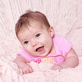 Cute baby girl. Portrait of cute baby girl lying on soft pink blanket Stock Photo