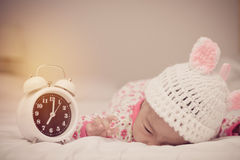 Cute baby girl and alarm clock wake up in the morning.  royalty free stock photos