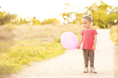 Cute baby girl with balloon outdoors Royalty Free Stock Photos