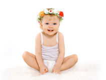 Cute baby girl. Cute beautiful blonde baby girl with floral wreath on his head, joyful happy child on a white background Stock Image