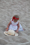 Cute baby girl in a beige hat sitting and playing on the beach Stock Photos