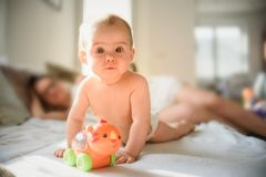 Cute baby girl on belly on couch in diaper with a toy on sofa royalty free stock images