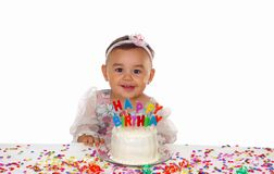 Cute Baby Girl and Birthday Cake. An adorable baby girl smiles over a vanilla-frosted birthday cake topped with colored letter candles royalty free stock photo