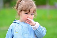 Cute baby girl with blonde curly hair outdoors. Royalty Free Stock Images