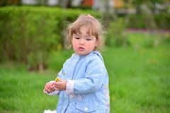 Cute baby girl with blonde curly hair outdoors. Stock Images