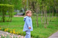 Cute baby girl with blonde curly hair outdoors. Royalty Free Stock Image