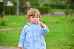 Cute baby girl with blonde curly hair outdoors. Stock Photos