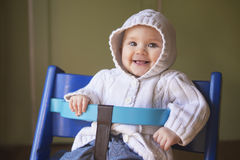 Cute baby girl in a blue chair. Adorable baby girl in a white hoodie Royalty Free Stock Image