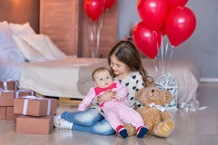 Cute baby girl celebrating birth day together close to red balloons.Lovely scene of baby on sofa divan with presents and Stock Images