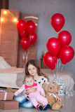 Cute baby girl celebrating birth day together close to red balloons.Lovely scene of baby on sofa divan with presents and Stock Photos