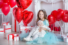 Cute baby girl celebrating birth day together close to red balloons.Lovely scene of baby on sofa divan with presents and royalty free stock photography