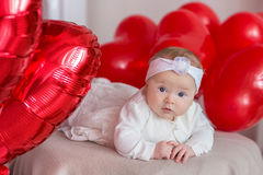 Cute baby girl celebrating birth day together close to red balloons.Lovely scene of baby on sofa divan with presents and Royalty Free Stock Image