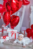 Cute baby girl celebrating birth day together close to red balloons.Lovely scene of baby on sofa divan with presents and Royalty Free Stock Photos
