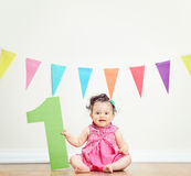 Cute baby girl celebrating her first birthday. Seated on the floor at home shot with tilt and shift lens Royalty Free Stock Photo