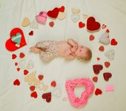 Cute baby girl. Childhood happiness.Valentines day. Love. Portrait of happy little child. Small girl among red hearts stock image