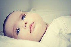 Cute baby girl. Close up of pretty infant face looking happy Royalty Free Stock Photos
