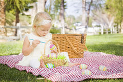 Cute Baby Girl Coloring Easter Eggs on Picnic Blanket Stock Images