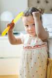Baby girl combing her hair in bedroom Royalty Free Stock Photo
