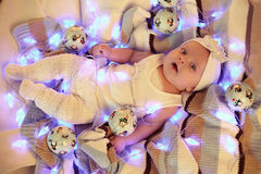 Cute baby girl in cozy clothes laying on plaid, among Christmas balls Stock Photo