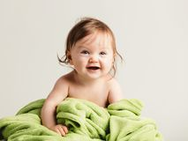 Cute baby girl with cozy green blanket smiling. Happy childhood Royalty Free Stock Photos