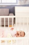 Cute baby girl in crib royalty free stock photos