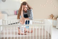 Cute baby girl in crib and young mother. Suffering from postnatal depression at home royalty free stock images