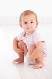 Cute baby girl crouching on floor Stock Image