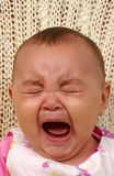 Cute Baby Girl Crying. Vertical portrait of an adorable baby girl crying royalty free stock photo