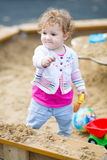 Cute baby girl digging in sand on a playground Royalty Free Stock Photo