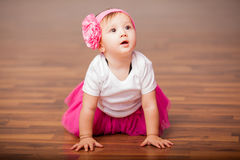 Cute baby girl dressed as ballerina. Portrait of a gorgeous little baby girl dressed up as a ballerina and sitting in the dance floor Royalty Free Stock Images