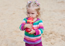 Cute baby drinking from a bottle. Cute baby girl drinking from a bottle of red in nature stock photos