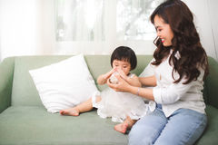 Cute baby girl drinking milk at home with her mom. Stock Photos