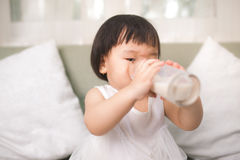 Cute baby girl drinking milk with milk mustache at home Royalty Free Stock Photo