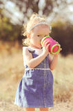 Cute baby girl drinking outdoors Royalty Free Stock Photography