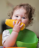 Cute baby girl eating corn Royalty Free Stock Photography