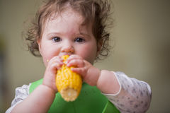 Cute baby girl eating corn Royalty Free Stock Photos