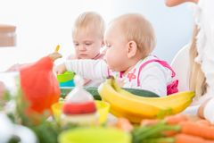 Cute baby girl eating healthy solid food in a modern daycare cen. Portrait of a cute baby girl with blue eyes eating healthy solid food, while sitting in a high Stock Photo