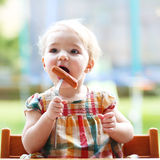 Cute baby girl eating sausage from fork Royalty Free Stock Image