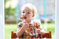 Cute baby girl eating sausage from fork stock photo