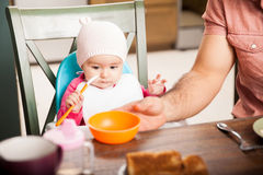 Cute baby girl eating soft food at home Royalty Free Stock Images