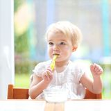 Cute baby girl eating yogurt from spoon stock photos