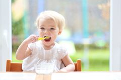 Cute baby girl eating yogurt from spoon Stock Images