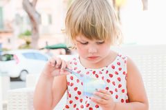Cute baby girl eats frozen yogurt with ice cream Royalty Free Stock Photo