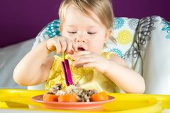 Cute baby girl eats hands chicken. With carrots on childrens table stock photo