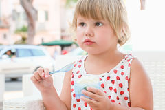 Cute baby girl eats yogurt with ice cream and fruits Stock Images